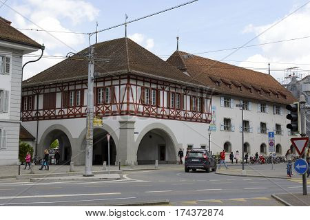 LUCERNE SWITZERLAND - MAY 04 2016: A Building with arcades under which the passage leads to Spreuer Bridge. Ancient armory of Lucerne nowadays it houses the Museum of History is shown in a distance