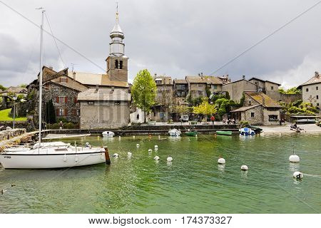 YVOIRE FRANCE - MAY 24 2013: Church tower over a medieval city. Sailboat and other boats are moored at the marina and on the shore of the lake a few people in the distance you can see
