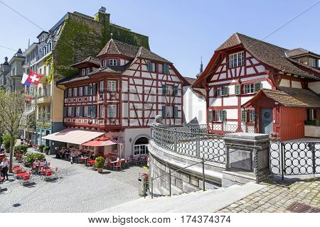 LUCERNE SWITZERLAND - MAY 06 2016: Half-timbered houses in one of them on the ground floor is a restaurant in front of which at the tables several people spend a nice time