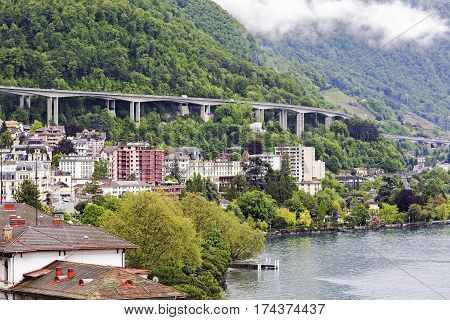 MONTREUX SWITZERLAND - MAY 22 2013: Highway on a hill was built over city buildings but very close to the shoreline of Lake Geneva. From the mountains coming clouds can be seen.