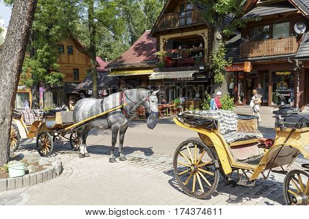 ZAKOPANE POLAND - SEPTEMBER 12 2016: Horse carriage at street Krupowki awaits tourists to perform a ride around the city. The rides such carriages with sightseeing are a tourist attraction.