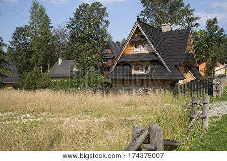 ZAKOPANE POLAND - SEPTEMBER 12 2016: Houses built in the style of mountain cottage can be seen behind the undeveloped meadow. These houses are surrounded by bushes and trees.