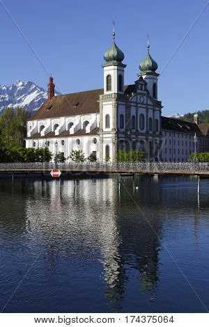LUCERNE SWITZERLAND - MAY 05 2016: Jesuit Church located by the Reuss river in old town is shown in a morning light. This church is one of the most visited tourist attractions in the city