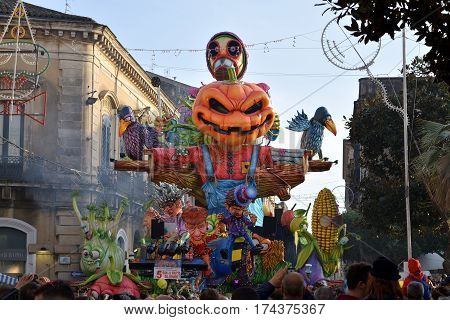 Acireale (CT) Italy - February 28 2017: allegorical float depicting a scarecrow with a pumpkin head and other vegetable's shaped characters during the carnival parade along the streets of Acireale