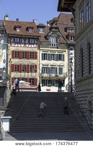 LUCERNE SWITZERLAND - MAY 08 2016: Stairs that lead to the square in the old town. Facades of two historic buildings can be seen in bright sunlight there are also some people.