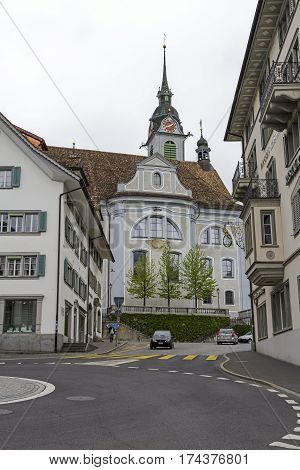 SCHWYZ SWITZERLAND - MAY 09 2016: The baroque church St. Martin that was inaugurated in the year 1774 is seen between the two buildings from the small roundabout.