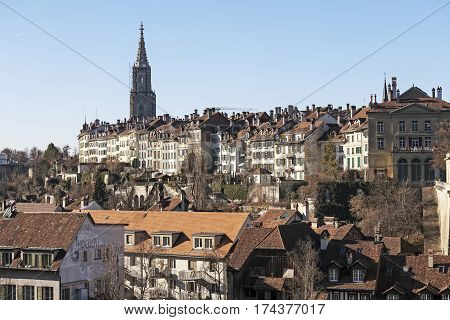 BERN SWITZERLAND - DECEMBER 26 2015: The facades of historic buildings and a high church tower shows a significant a density of development city