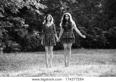 Two young smiling women levitate in the park black and white colors