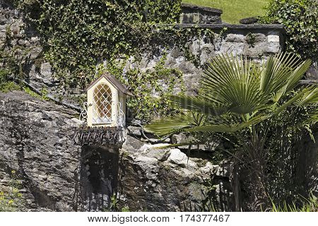 WEGGIS SWITZERLAND - MAY 05 2016: The tiny chapel is located on a rock under a stone fence in the vicinity of various plants. The origin of this tiny sacral architecture is not widely known.