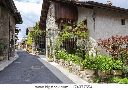 YVOIRE FRANCE - MAY 24 2013: The view along the street of the medieval town and its stony houses in which on a ground floor operate stores and restaurants. There are a lot of plants and flowers.