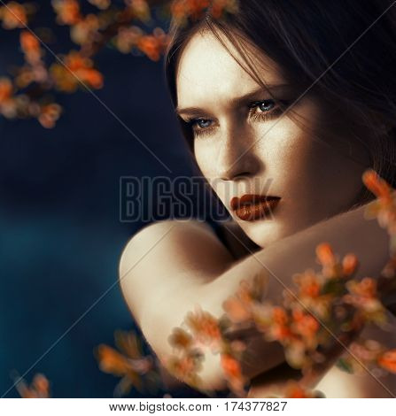Close-up portrait of a beautiful young woman with a thoughtful gaze at the open air on dark blue background and bokeh leafs at foreground