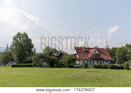 ZAKOPANE POLAND - SEPTEMBER 13 2016: Two classic houses that was built in the style of the region are hidden between bushes and trees and can be seen behind the green meadow