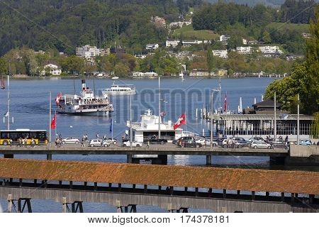 LUCERNE SWITZERLAND - MAY 06 2016: Roofed Chapel Bridge traffic jam on the Seebruecke and many boats on Lake Lucerne together with many houses among trees it shows the tourist nature of the town