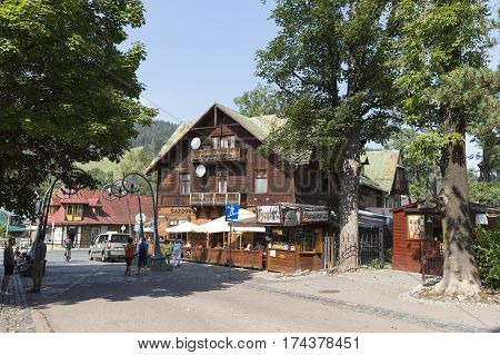 ZAKOPANE POLAND - SEPTEMBER 12 2016: Wooden building at the street that houses well known restaurant. In outer restaurant behind the wooden fence a few people can be seen