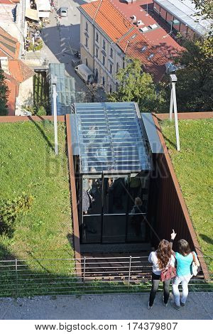 LJUBLJANA SLOVENIA - OCTOBER 12: Two Tourists Waiting For Funicular Tram in Ljubljana on OCTOBER 12 2014. Funicular Railway Transport To Castle at Hill in Ljubljana Slovenia.