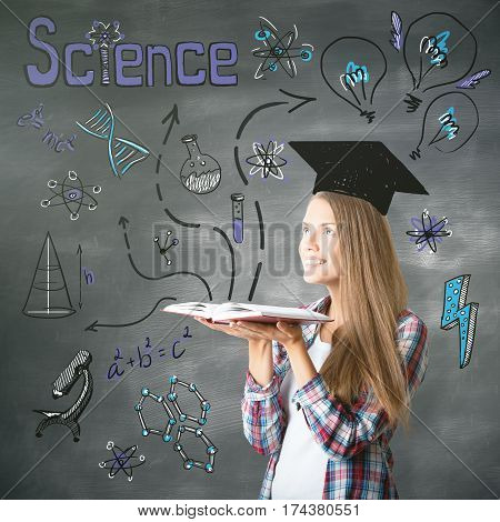 Attractive cheerful young caucasian woman with open book drawn mortarboard and other education related drawings. Knowledge concept