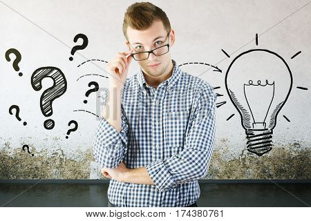Thinking man with drawn question marks and lamp on concrete background. Idea concept