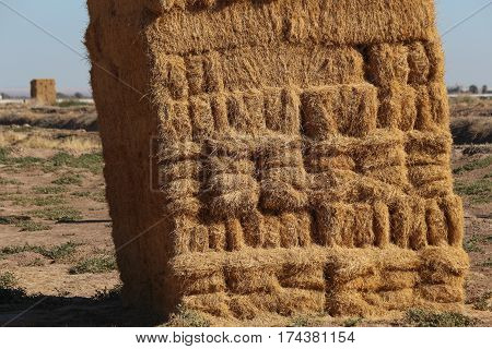 Large square haystack constructed of layers of haybales, slightly leaning, in a field.