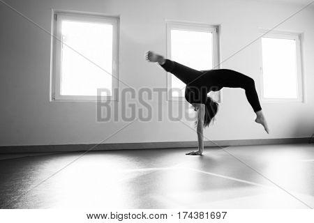 young dancer woman practice floor jump on modern ballet class indoor shot in bw