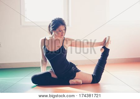 young dancer woman doing stretching on ballet class indoor shot