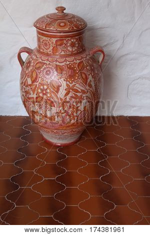 One large Tonala-style Mexican lidded jar with floral pattern, standing against a white wall on a red tile floor, copy space.