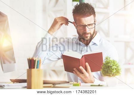 Close up portrait of handsome caucasian male reading book at modern workplace with decorative plant and other items. Knowledge concept