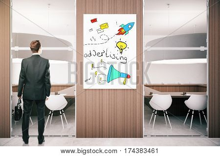 Back view of businessman in modern conference room with ad poster on wooden wall. Advertismenet concept. 3D Rendering