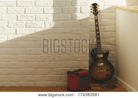 White brick interior with guitar amplifier blank wall and sunlight. Music concept