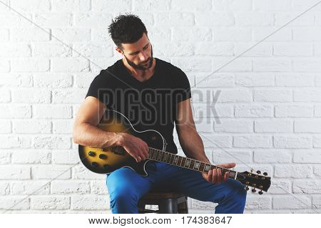 Portrait of attractive caucasian man playing the guitar on white brick wall background. Rehearsal concept