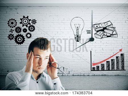 Pensive young businessman in brick room with drawn cogwheels clock lamps charts and money. Business idea concept. 3D Rendering