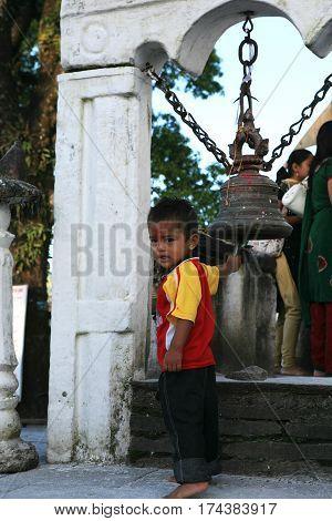 POKHARA, NEPAL. 25 September 2008:  Little boy-Hindu pilgrim at a sacred bell at the temple of goddess Durga. Himalayas, Pokhara, Nepal.