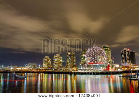 The city of Vancouver at night with boats on False Creek.