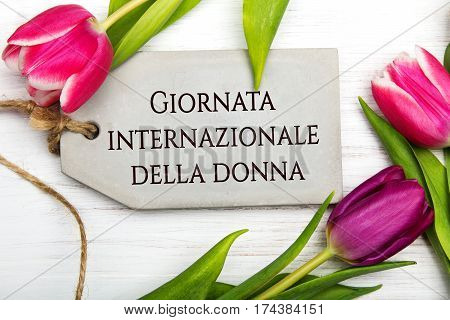 Women's day card with Italian words 'Giornata internazionale della donna'. Tulip flower and small heart on white wooden background