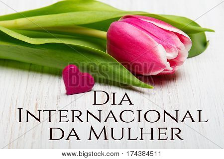 Women's day card with Portuguese words 'Día Internacional da Mulher'.Tulip flower and small heart on white wooden background