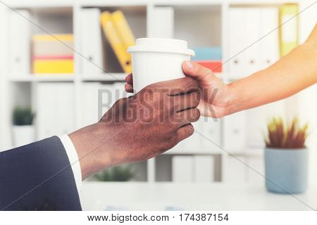 Close up of a hand of a woman giving a paper cup of coffee to the boss sitting at the table. Toned image.