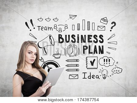 Portrait of a blond woman with a cleavage holding a tablet computer and standing near a concrete wall with a business plan sketch on it.