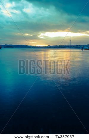 Deep blue tones in water and sky and sunset colors over the bay Russell New Zealand.