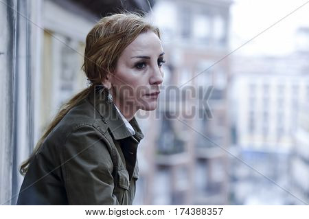 lost and sad woman at home balcony suffering depression looking thoughtful and solitary in female depression concept and sadness emotion dramatic facial expression