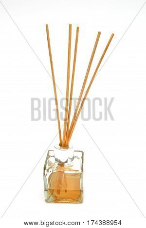 Reed diffuser with reed sticks in a bottle of scented oil on white background