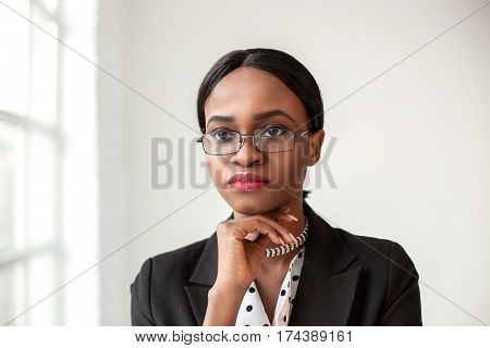 Close-up shot of pretty african american businesswoman wearing glasses. Office shot.