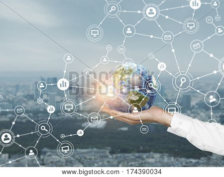 Close up of a hand of a businessman holding the Earth. There is a large network hologram in the air. Toned image.