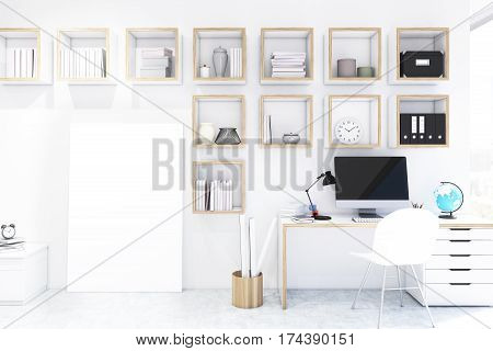 Desk with computer in a home office with square bookshelves on a white wall. A vertical poster is standing in the corner. White chair is near the desk. 3d rendering. Mock up