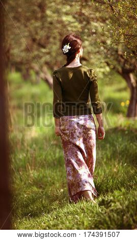 Romantic moments. Young girl walks in a spring flowering garden in a long skirt over green grass.