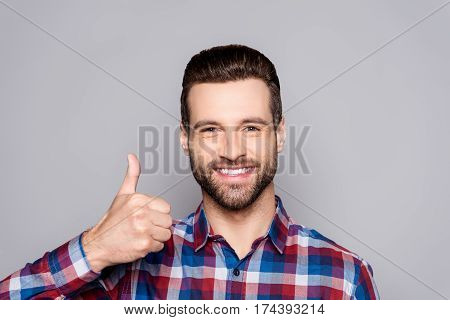 Young Handsome Man Smiling And Gesturing  Thumbs Up Sign Against Gray Background