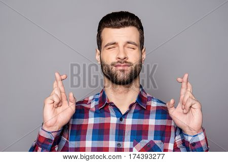 A Portrair Of A Young Man With Crossed Fingers And Closed Eyes Praying For Risky Business