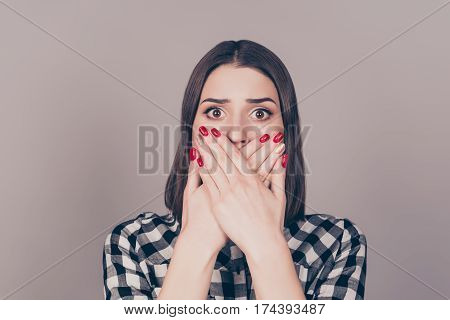 Close Up Of Pretty Young Surprised Woman Covering Mouth With Her Hands Standing Against Gray Backgro