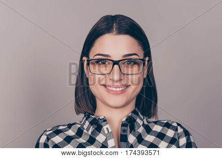 Young Pretty Woman With Beaming Smile In Glasses And Checkered Shit Looking At Camera