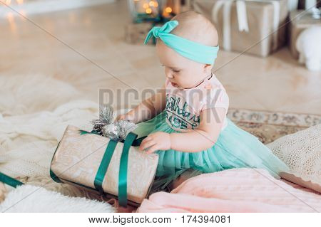 Little baby girl in dress with gifts in studio