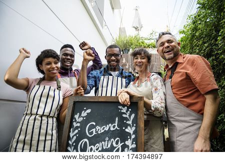 Diverse People with Grand Opening Sign First Day of Business
