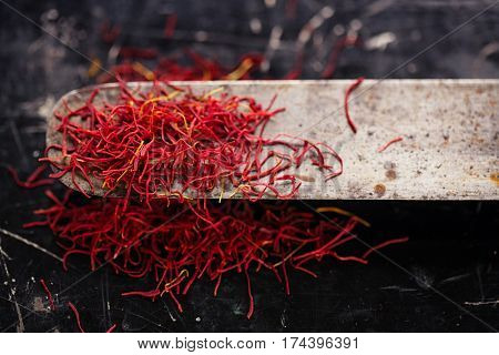 saffron space threads in vintage knife with dark metal background